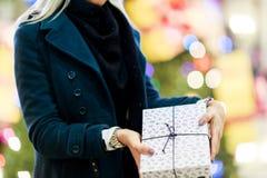 Bild der Frau im Mantel mit Geschenkbox auf Hintergrund des Weihnachtsbaums stockfotografie