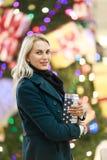Bild der Frau im Mantel mit Geschenkbox auf Hintergrund des Weihnachtsbaums im Speicher Stockfotografie