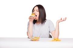 Bild der Frau mit Früchten und Hamburger in der Front auf weißem BAC Lizenzfreies Stockbild