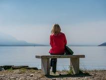 Bild der Frau mit der roten Jacke, die auf einer Steinbank betrachtet See maggiore sitzt stockbild