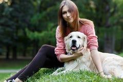 Bild der Frau und des Hundes, die auf Rasen sitzen Lizenzfreie Stockfotografie