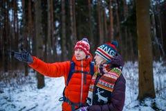 Bild der Frau und des Mannes, die Hand vorwärts im Winterwald zeigen Stockbilder