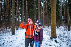 Bild der Frau und des Mannes, die Hand vorwärts im Winterwald zeigen Stockfotos