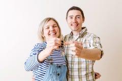 Bild der Frau und des Mannes mit Schlüsseln von der Wohnung gegen leere Wand Stockfoto