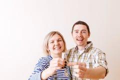 Bild der Frau und des Mannes mit Schlüsseln von der Wohnung gegen leere Wand Stockbilder
