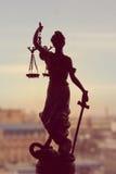 Bild der Göttin Themis oder Dame Justice, das auf dem Fenster draußen hält Klingenaugenbinde auf dem Hintergrund der Stadt steht Stockbild