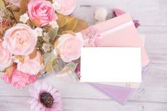 Bild der Geschenkbox mit rotem Band mit Blume und Gutschein an Lizenzfreies Stockbild