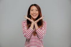 Bild der glücklichen asiatischen Frau in der Strickjacke, die Kamera betrachtet Stockfotos
