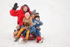 Bild der glücklichen Familie mit der Tochter und Sohn, die auf Schläuche im Winter sitzen Lizenzfreie Stockfotografie