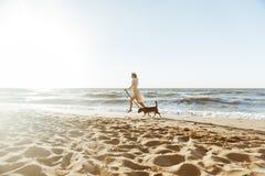 Bild der glücklichen Frau im Strohhut, laufend mit ihrem braunen Hund entlang der Küste lizenzfreie stockfotos