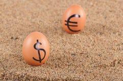 Bild der großen weißen Eier mit dollarand Eurozeichen auf einem Sand. Lizenzfreies Stockfoto