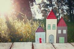 Bild der hölzernen bunten Hausdekoration der Weinlese auf Holztisch vor Landschaftswald Stockbilder