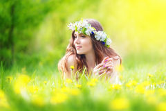 Bild der hübschen Frau hinlegend auf Löwenzahnfeld, glückliches che Lizenzfreie Stockfotos