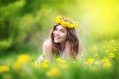 Bild der hübschen Frau hinlegend auf Löwenzahnfeld, glückliches che stockfotos