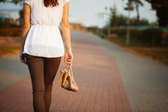 Bild der Hand der jungen Frau mit Schuhen im Park. Stockbilder
