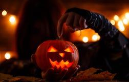 Bild der Hexe mit dem langen Haar, das Hand auf Halloween-Kürbis zeigt Lizenzfreie Stockfotografie