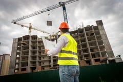 Bild der hinteren Ansicht des Bauingenieurs in Kontrollebau der grünen Sicherheitsweste und des roten Hardhat des Neubaus lizenzfreie stockbilder