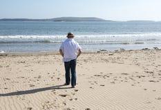 Bild der hinteren Ansicht eines reifen Mannes, der entlang den Strand geht Stockfotografie