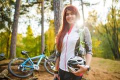 Bild der jungen athletischen Frau mit Sturzhelm auf Hintergrund des Fahrrades am Herbstwald Stockbilder