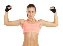 Bild der jungen sportlichen Frau, die ihr Bizeps lokalisiert auf Weiß zeigt Lizenzfreie Stockbilder
