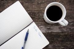 Bild der Kaffeetasse mit Notizbuch und des Stiftes auf einem alten Holztisch Lizenzfreie Stockfotos