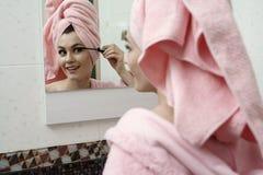 Bild der lächelnden flirtend Frau, die Wimperntusche verwendet Stockbilder