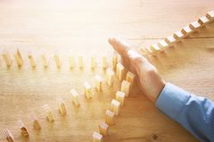 Bild der männlichen Hand den Domino-Effekt stoppend Retrostilbildexekutive- und -Risikokontrollekonzept stockfotografie