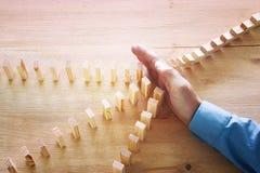 Bild der männlichen Hand den Domino-Effekt stoppend Retrostilbildexekutive- und -Risikokontrollekonzept stockfoto