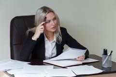 Bild der nachdenklichen Geschäftsfrau mit großem Notizblock in der Klage, die am Tisch mit Dokumenten sitzt Stockfoto
