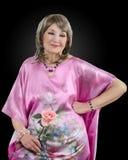 Bild der nachdenklichen 76-jährigen Frau hat auf rosa silk Robe Stockbild