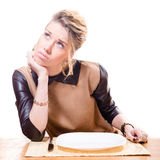 Bild der schönen jungen attraktiven blonden Frau, die Gabel in ihrer Hand oben schaut, leere Platte lokalisiert auf weißem Hinterg Stockbilder