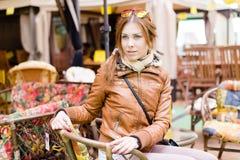 Bild der schönen jungen Frau, die auf den weichen Stühlen wählen Möbel für das Haus im Marktporträt sitzt Lizenzfreies Stockbild
