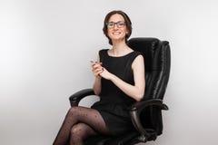 Bild der Schönheit im schwarzen Kleid, das im Lehnsessel sitzt lizenzfreies stockfoto