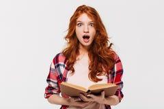 Bild der Shocked Ingwerfrau im Hemd, das Buch hält Lizenzfreies Stockfoto