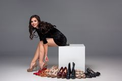 Bild der sitzenden Frau versuchend auf hochhackigem Lizenzfreie Stockfotografie