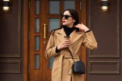 Bild der stilvollen schönen weiblichen stehenden Außenseite, tragender beige Mantel, schwarzes Hemd, moderne Sonnenbrille, berühr stockbild