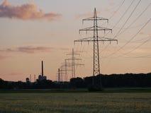 Bild der Stromleitung während des Sonnenuntergangs mit Kraftwerk stockfotografie