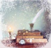 Bild der weißen Feder, des Tintenfasses und der alten Bücher Stockfoto
