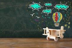 Bild des alten hölzernen Flugzeugspielzeugs auf Holztisch vor Satz Informationsgraphiken über strukturierter Tafel Stockfotografie