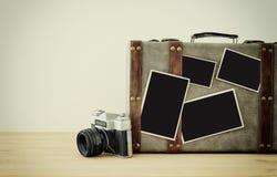Bild des alten Weinlesegepäcks, der alten Fotokamera der Weinlese und der leeren Fotos für Fotografiemontagemodell über Bretterbo Lizenzfreies Stockbild