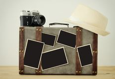 Bild des alten Weinlesegepäcks, des Fedorahutes, der alten Fotokamera der Weinlese und der leeren Fotos für Fotografiemontagemode Stockfoto