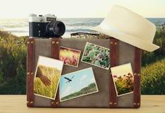 Bild des alten Weinlesegepäcks, des Fedorahutes und der alten Fotokamera der Weinlese mit Naturfotos über Bretterboden Lizenzfreie Stockfotos
