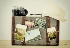 Bild des alten Weinlesegepäcks, des Fedorahutes und der alten Fotokamera der Weinlese mit Naturfotos über Bretterboden Stockfotos