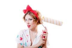 Bild des attraktiven blonden Pinupmädchens mit den grünen Augen u. roten Lippen, die Kissen überrascht u. aufgeregt halten Stockbild