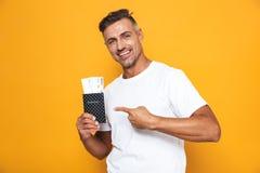 Bild des bärtigen Mannes 30s in den weißen T-Shirt Holdingpass- und -reisekarten lizenzfreie stockfotos