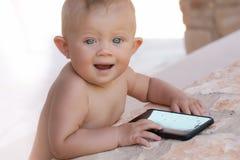 Bild des Babys draußen spielend mit Telefon-, Liebes- und Glückkonzept Lizenzfreie Stockfotografie