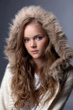 Bild des bezaubernden jungen Mädchens, das in der Pelzhaube aufwirft Stockfotografie