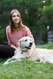 Bild des Brunette und des Hundes, die auf Rasen sitzen Stockfotos
