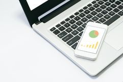 Bild des Computerlaptops, Mobiltelefon mit Diagramm auf Arbeitsplatz Stockbild