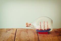 Bild des dekorativen Bootes in der Flasche auf Holztisch Verrostete, alte, symbolische Kette von einem Anker mit Booten verblaßte Stockfotos